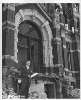Mayor Steven Juba standing in front of partially demolished City Hall building, April 27, 1962