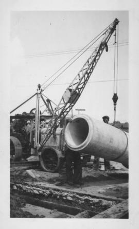 Men and crane lifting concrete form