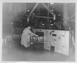 Man loading machinery with shell cases at Dominion Bridge Company