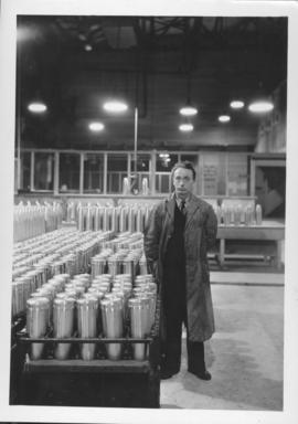 Man standing beside shell cases at Dominion Bridge Company