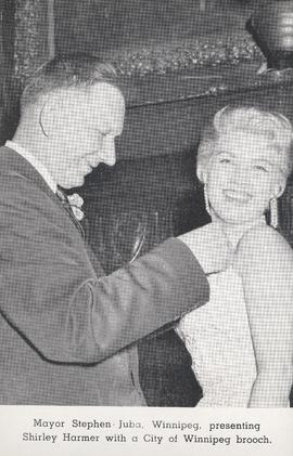 Mayor Stephen Juba, Winnipeg, presenting Shirley Harmer [Singer] with a City of Winnipeg brooch