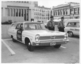 Policemen beside police car parked in front of the Public Safety Building