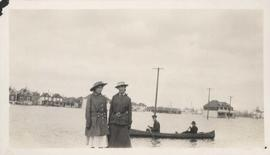 Women standing on flooded residential street with men in canoe, 1916 Flood, Norwood