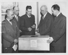 Mayor Garnet Coulter hammering shut a wooden box containing film and projector from Winnipeg phot...