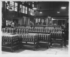 Shell cases on workbenches and carts at Dominion Bridge Company