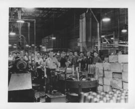 Workmen standing by conveyor belt and boxes of shell cases at Dominion Bridge Company