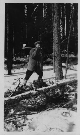 Man with ax at city wood camp, Greater Winnipeg Water District Railway