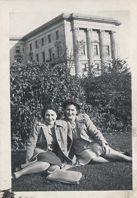 Two students sitting on lawn with Normal School in background