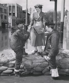 1950 Flood - Red Cross Nurse distributes free cigarettes to dykers