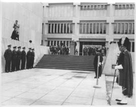 Exterior of Public Safety Building, Speaker at podium, Policemen in uniform lined up on both side...
