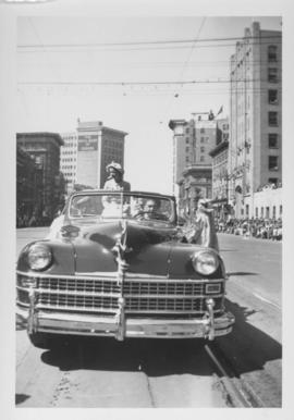 Woman riding in an automobile, Winnipeg's 75th Anniversary Parade