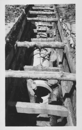 Men and concrete form in trench under wooden support