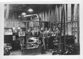 Group of workmen standing behind machinery at Dominion Bridge Company