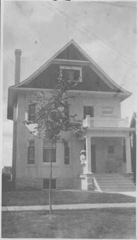 Exterior of home, 146 Spence Street, with woman sitting on porch railing