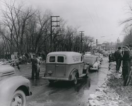 Vehicles driving down flooded street in the vicinity of Shaarey Zedek Synagogue, 1950 Flood