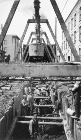 View of men mucking trench for 48-inch diameter Branch 1 aqueduct at Sta. 169+00 on Pacific Avenu...