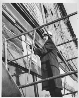 Mayor Stephen Juba, wearing a hard hat, on scaffolding against building being demolished, with crowbar in hand